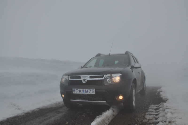 Our Dacia Duster on the road back from the glacier, between walls of about 2m high snow,